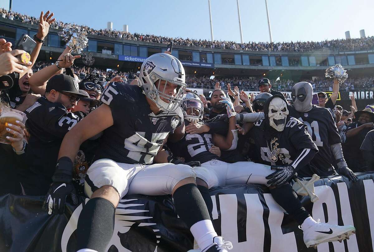"""OAKLAND, CALIFORNIA - NOVEMBER 03: Josh Jacobs #28 and Alec Ingold #45 of the Oakland Raiders celebrates with fans in the """"The Black Hole"""" after Jacobs scored on a two yard touchdown run against the Detroit Lions during the second quarter of an NFL football game at RingCentral Coliseum on November 03, 2019 in Oakland, California. (Photo by Thearon W. Henderson/Getty Images)"""