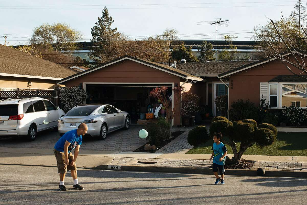 Edric Yamamoto and his son, Greyson Yamamoto, 7 play bounce outside their home in the Birdland neighborhood in Sunnyvale, Calif. Wednesday, Jan. 31, 2018. Yamamoto said that he doesn't mind the new Apple campus, which looms over his home.