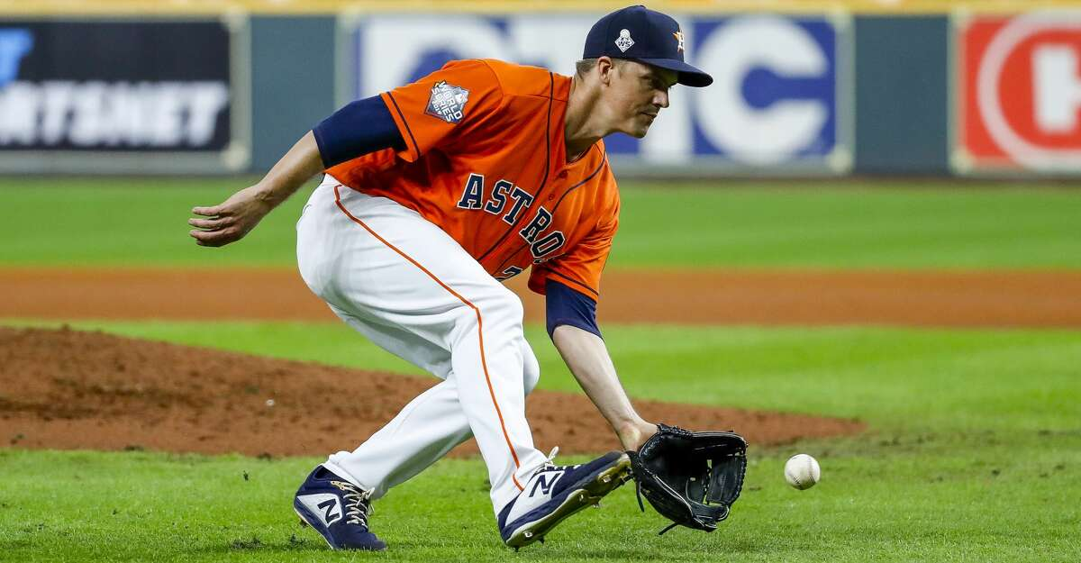 Houston Astros starting pitcher Zack Greinke (21) fields a ground ball from Washington Nationals second baseman Asdrubal Cabrera (13) during the fifth inning of Game 7 of the World Series at Minute Maid Park on Wednesday, Oct. 30, 2019, in Houston.
