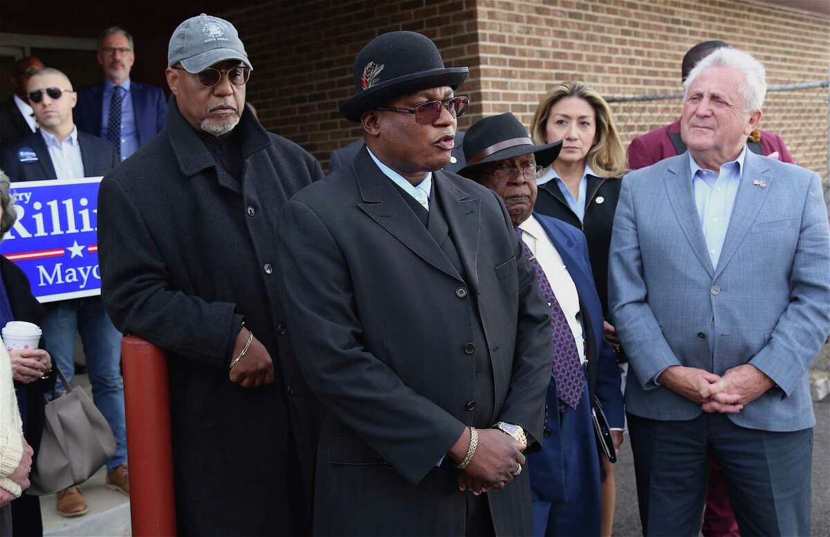 Richard Clark, pastor of Bethel AME Church, shares support for Mayor Harry Rilling, right, while Lindsay Curtis, pastor of Grace Baptist Church, at left, listens during a rally Sunday in South Norwalk.
