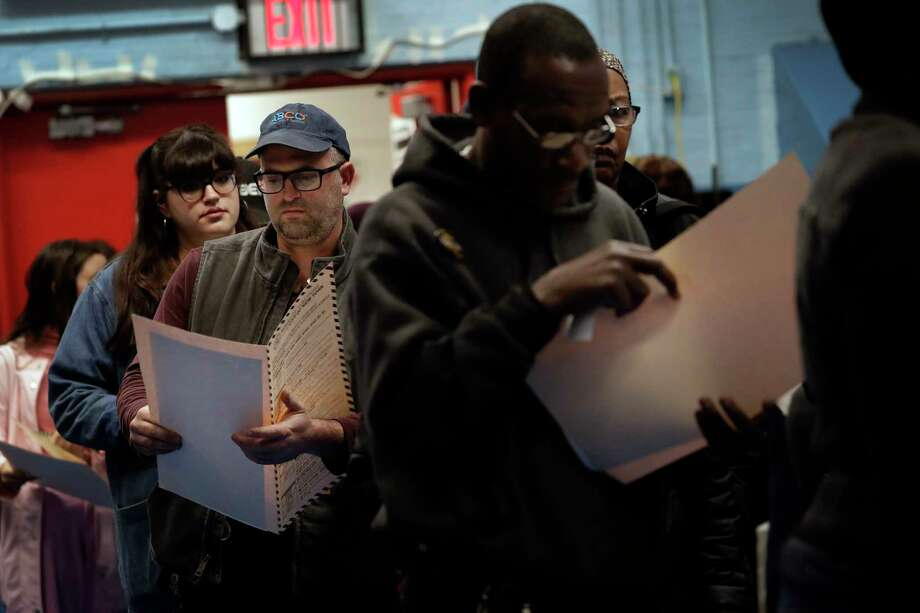 In this Nov. 6, 2018 file photo, voters read their ballot papers as they wait in line to cast their vote at P.S. 161 in Brooklyn borough of New York. A ballot measure will give New York City residents a chance to institute ranked choice voting in primaries and special elections. Under the system now in effect in cities such as San Francisco and Cambridge, Massachusetts as well as the entire state of Maine, voters can rank candidates in order of preference instead of choosing just one.(AP Photo/Wong Maye-E, File) Photo: Wong Maye-E / Copyright 2019 The Associated Press. All rights reserved.