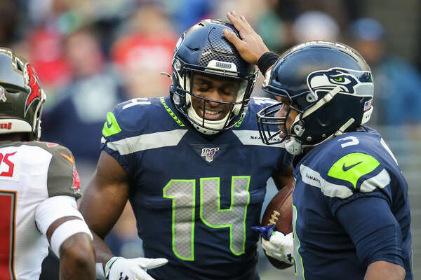 Russell Wilson pats Seattle Seahawks wide receiver D.K. Metcalf's helmet after he scored a 53-yard touchdown in the fourth quarter of Seattle's game against Tampa Bay, Sunday, Nov. 3, 2019 at CenturyLink Field. The Seahawks won 40-34 in overtime.