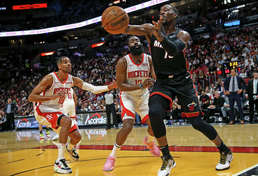 Miami Heat center Bam Adebayo (13) pass the ball against Houston Rockets guard James Harden (13) and Thabo Sefolosha (18) in the second quarter on Sunday, Nov. 3, 2019 at the AmericanAirlines Arena in Miami, Fla. (David Santiago/Miami Herald/TNS)