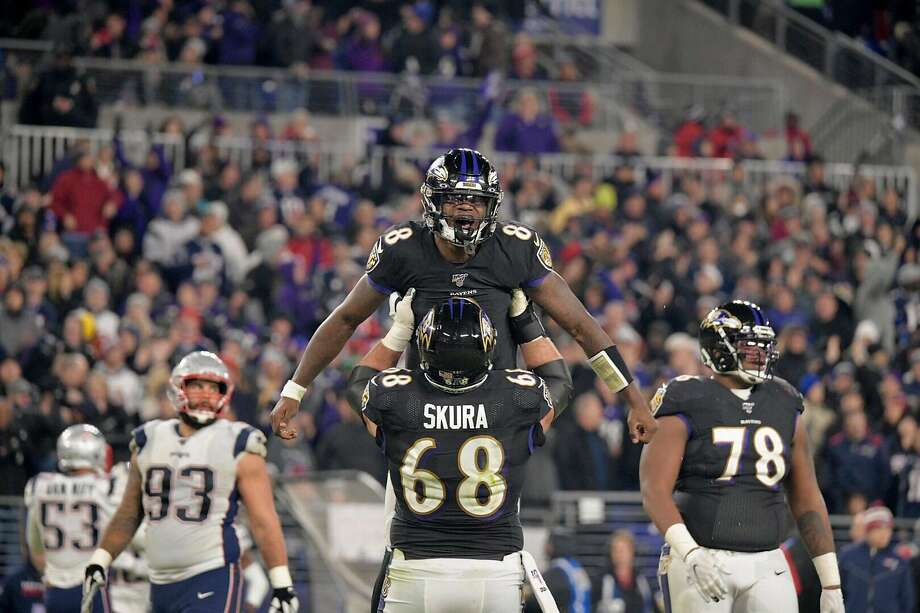 Baltimore Ravens' Matt Skura (68) lifts Lamar Jackson (8) in celebration during the second half against the New England Patriots on Sunday, Nov. 3, 2019 at M&T Bank Stadium in Baltimore, Md. (Karl Merton Ferron/Baltimore Sun/TNS) Photo: Karl Merton Ferron / TNS