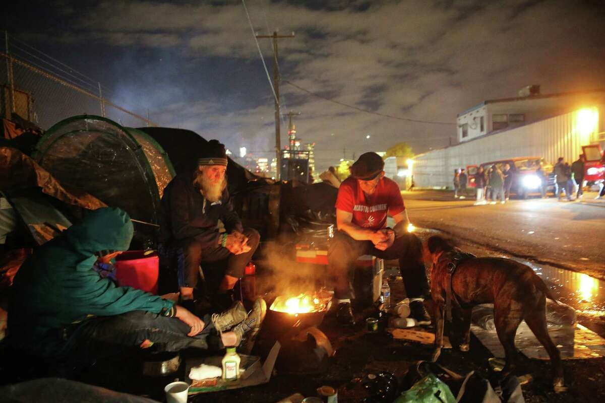 Robert VanGuilder, center, sits by a fire outside his tent in SoDo as the Union Gospel Mission Search and Rescue team hands out hot chocolate, food and other supplies from their vans across the street, Oct. 8, 2019.