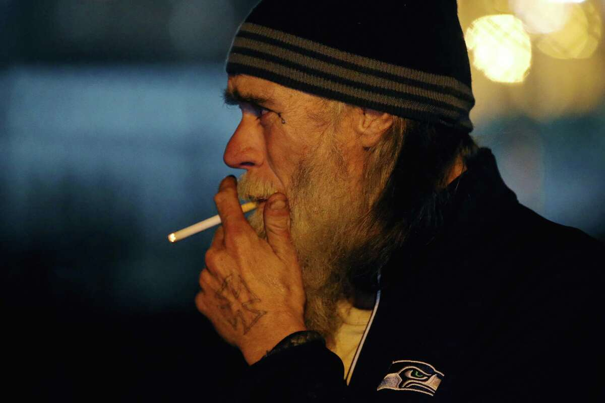 Robert VanGuilder smokes a cigarette as he chats with the Union Gospel Mission Search and Rescue team in SoDo, Oct. 8, 2019. The team visits the neighborhood once a week to hand out food and supplies to people living in tents and vehicles, Oct. 8, 2019.
