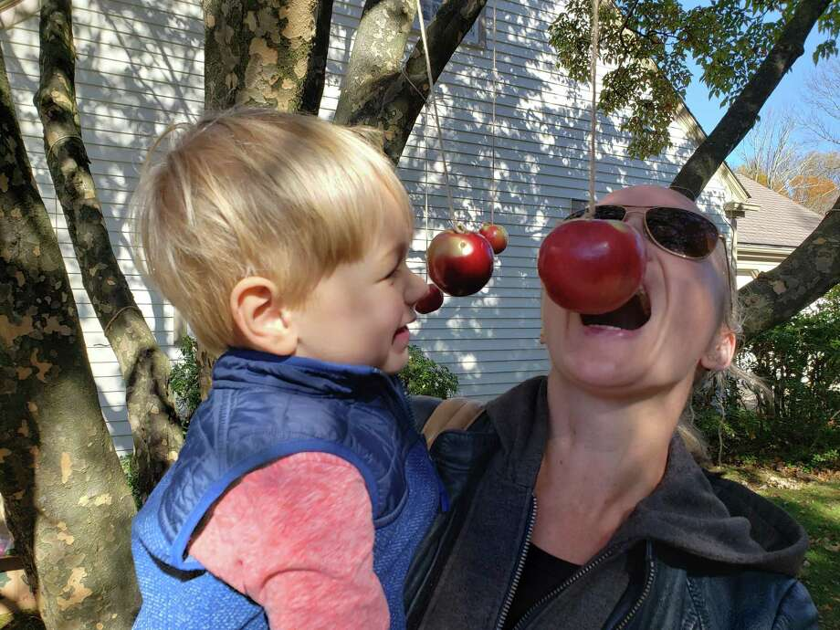 Tobey Wallace and 3-year-old Cameron Bangert of New Canaan, bob for apples. Photo: Sandra Diamond Fox / Connecticut Post