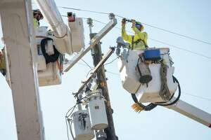 A worker for Source Power Services, contracted by Pacific Gas & Electric (PG&E), repairs a power transformer in Healdsburg, Calif., on Oct. 31, 2019.