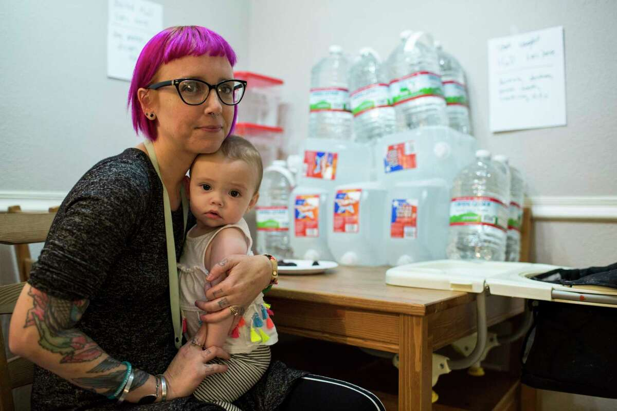 Jenny Church, a work-at-home mom in northeast Austin, poses with her child and the 16 gallons of water she boils and cools every day for her family and a pregnant friend. Approximately 100 Texas communities are living without clean water or wastewater services. Vote yes on Proposition 2 to help change that.