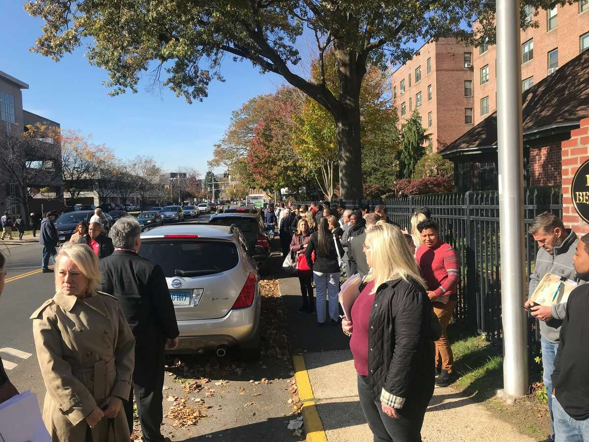 People stand across the street from the Stamford Courthouse after being evacuated on Monday, Nov. 4, 2019.