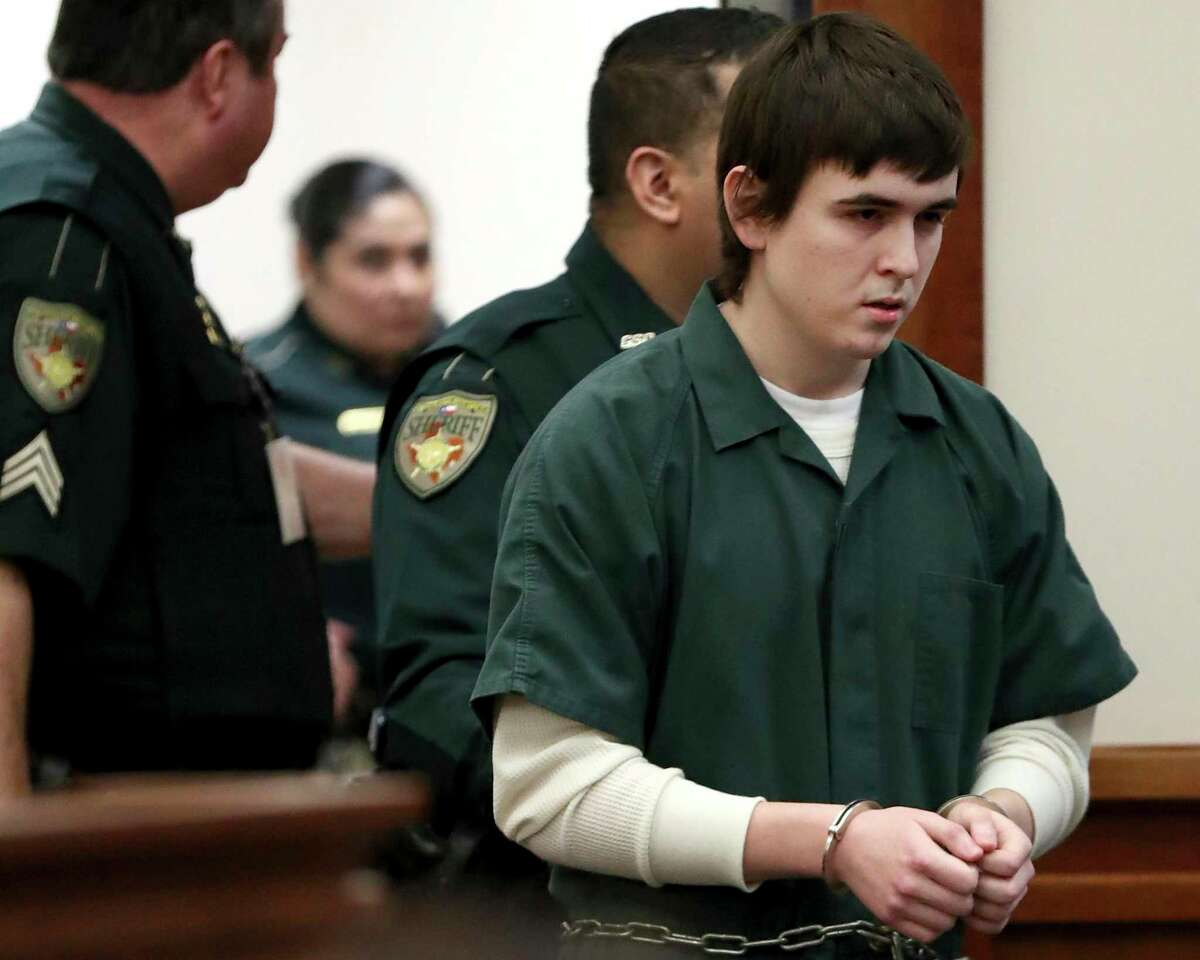 In this Feb. 25, 2019 file photo, Dimitrios Pagourtzis is escorted by Galveston County Sheriff's Office deputies into the jury assembly room for a change of venue hearing at the Galveston County Courthouse in Galveston, Texas. A judge in Texas has ordered another mental evaluation for the former Santa Fe High School student accused of opening fire on campus in a 2018 attack that left 10 people dead and 13 wounded. (Jennifer Reynolds/The Galveston County Daily News via AP, Pool, File)