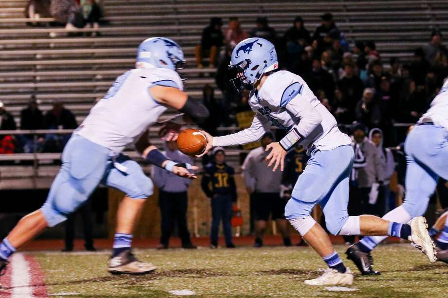 Meridian's Cam Metzger hands off to Brady Solano during last Friday's district semifinal vs. Ithaca. Photo: Daily News File Photo