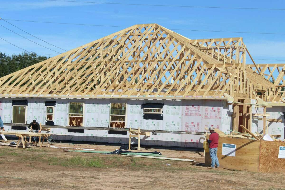 Construction workers work on a home at the new Copper Cove development off South Cherry Street. Copper Cove is a 52-home development, one of 15 developments currently planned to be built in Tomball.