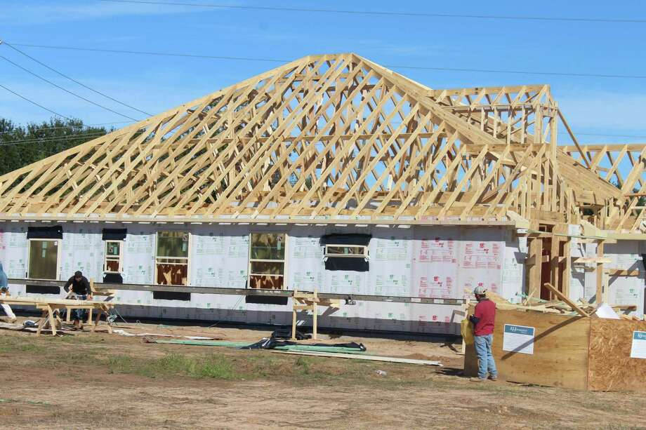 Construction workers work on a home at the new Copper Cove development off South Cherry Street. Copper Cove is a 52-home development, one of 15 developments currently planned to be built in Tomball. Photo: Paul Wedding