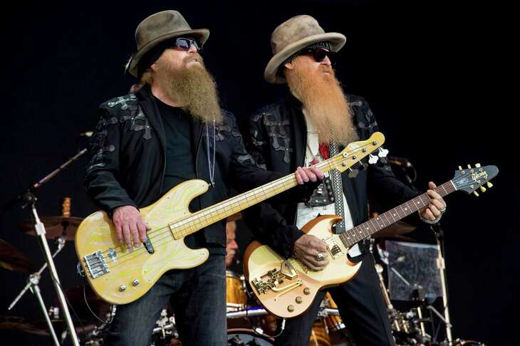 FILE - In this June 24, 2016, file photo, Dusty Hill, left, and Billy Gibbons from the rock band ZZ Top perform at the Glastonbury music festival at Worthy Farm, in Somerset, England. Joe Walsh will be joined by ZZ Top, Brad Paisley, Sheryl Crow, and Jason Isbell and The 400 Unit at his VetsAid music festival to benefit veterans. The award-winning musician announced Monday, Aug. 12, 2019, file photo, that tickets for the Nov. 10 concert at the Toyota Center in Houston will go on sale Friday. (Photo by Jonathan Short/Invision/AP, File)