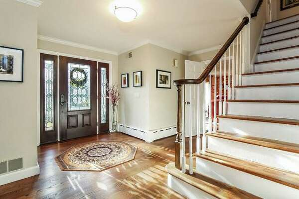 The front door and sidelights feature decorative leaded glass windows and opens into the foyer.