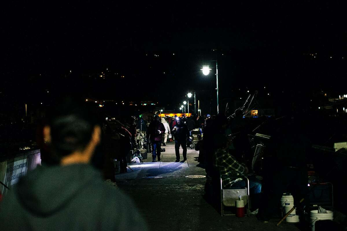 People walk along Pacifica Pier during opening day of California's recreational fishery for Dungeness crab season on Nov. 2, 2019.