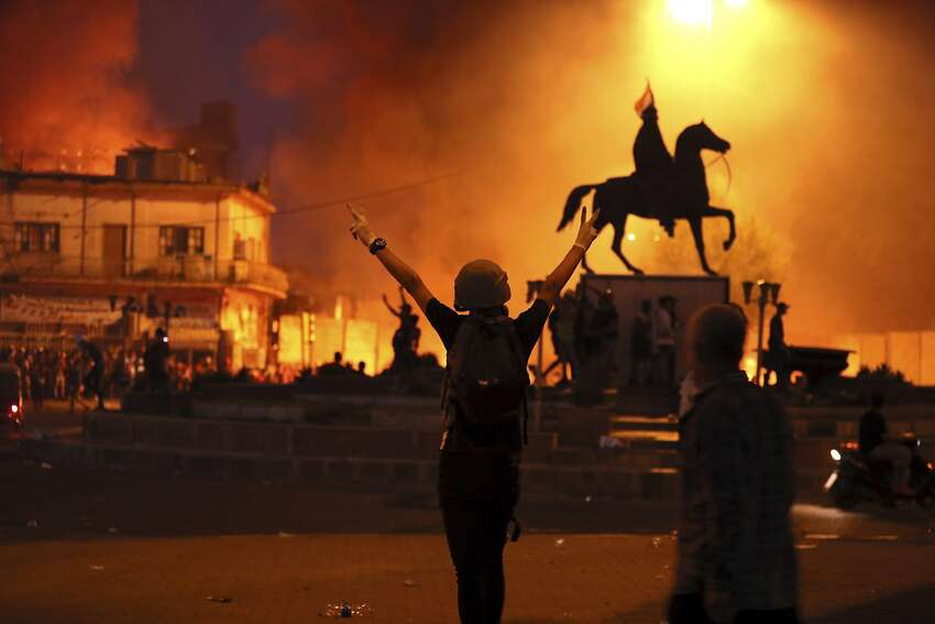 Demonstrators ignite fires while state security forces fire live ammunition and tear gas in Baghdad.