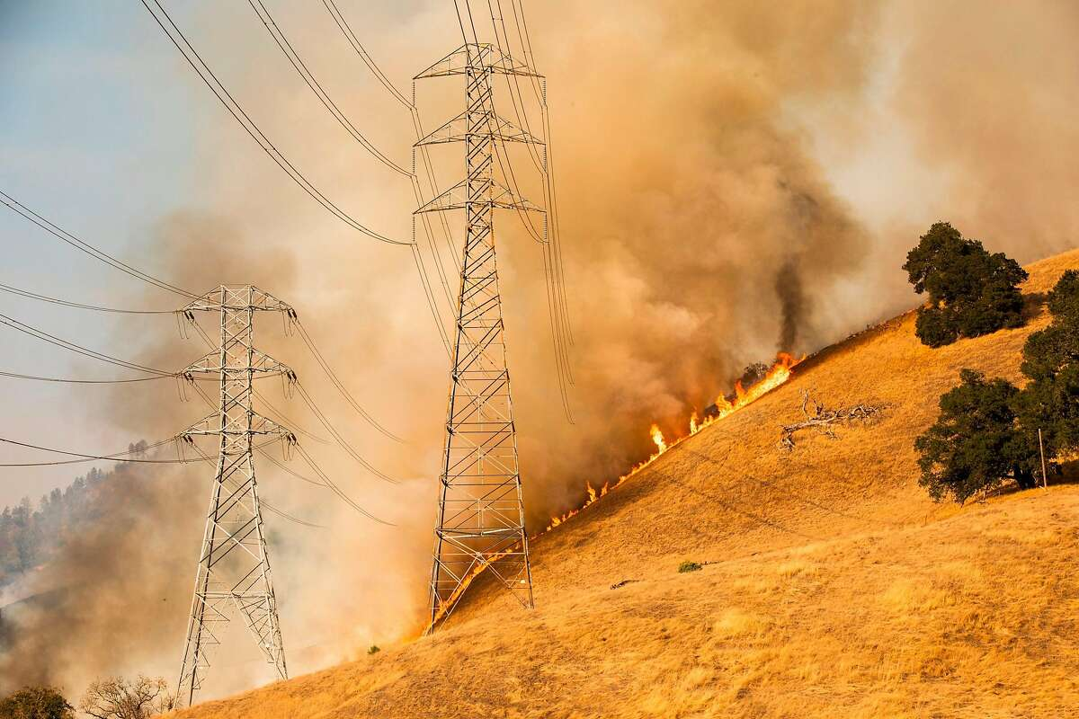 A back fire set by fire fighters burns a hillside behind PG&E power lines during firefighting operations to battle the Kincade Fire in Healdsburg, California on October 26, 2019.