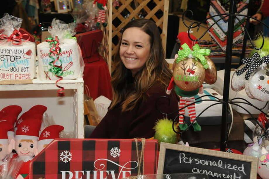 Jamie Frey of Rosewood Heights and some of the items she sold at Deck the Walls Craft Show at Civic Memorial High School in Bethalto, including holiday-themed toilet paper. More than 50 vendor booths were featured Saturday and Sunday at the event which helps fund the Civic Memorial High School prom and after prom celebrations.