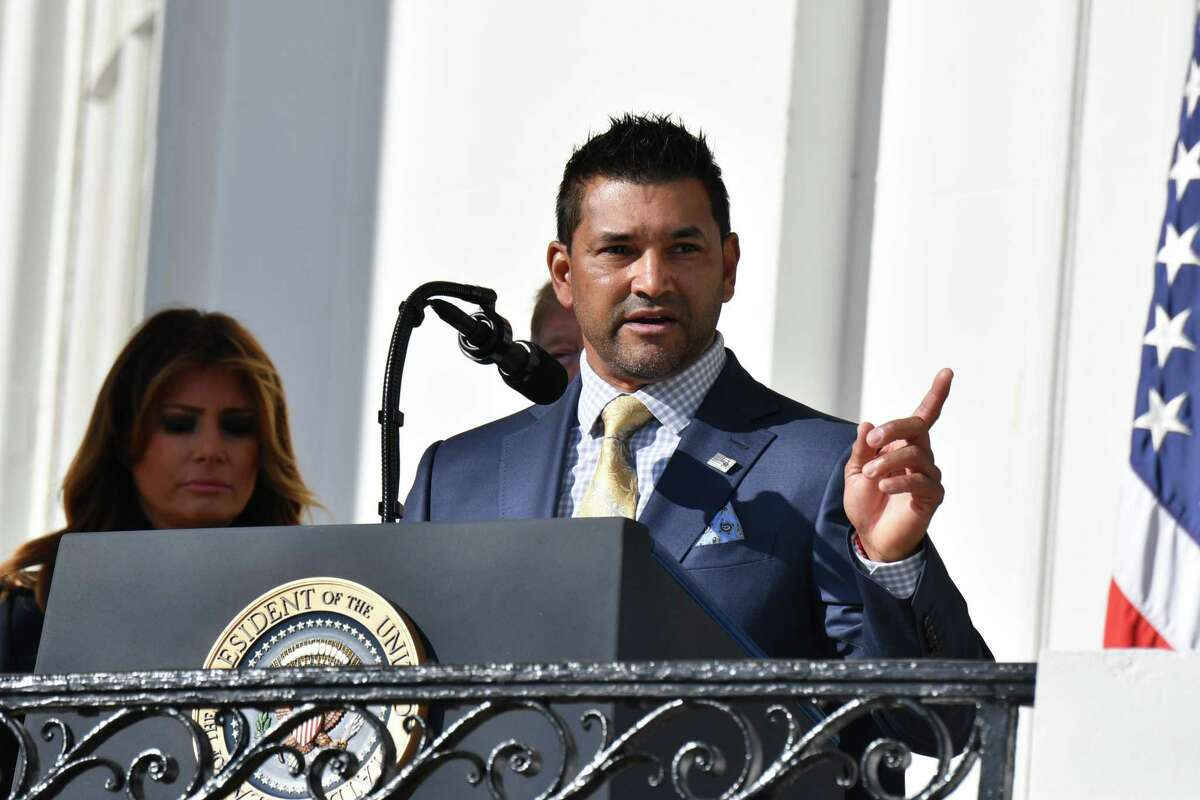 US President Donald Trump(behind) and First Lady Melania Trump(behind) stand with manager Dave Martinez as they welcome the 2019 World Series Champions, The Washington Nationals, to the White House on November 4, 2019 in Washington,DC. (Photo by Nicholas Kamm / AFP)