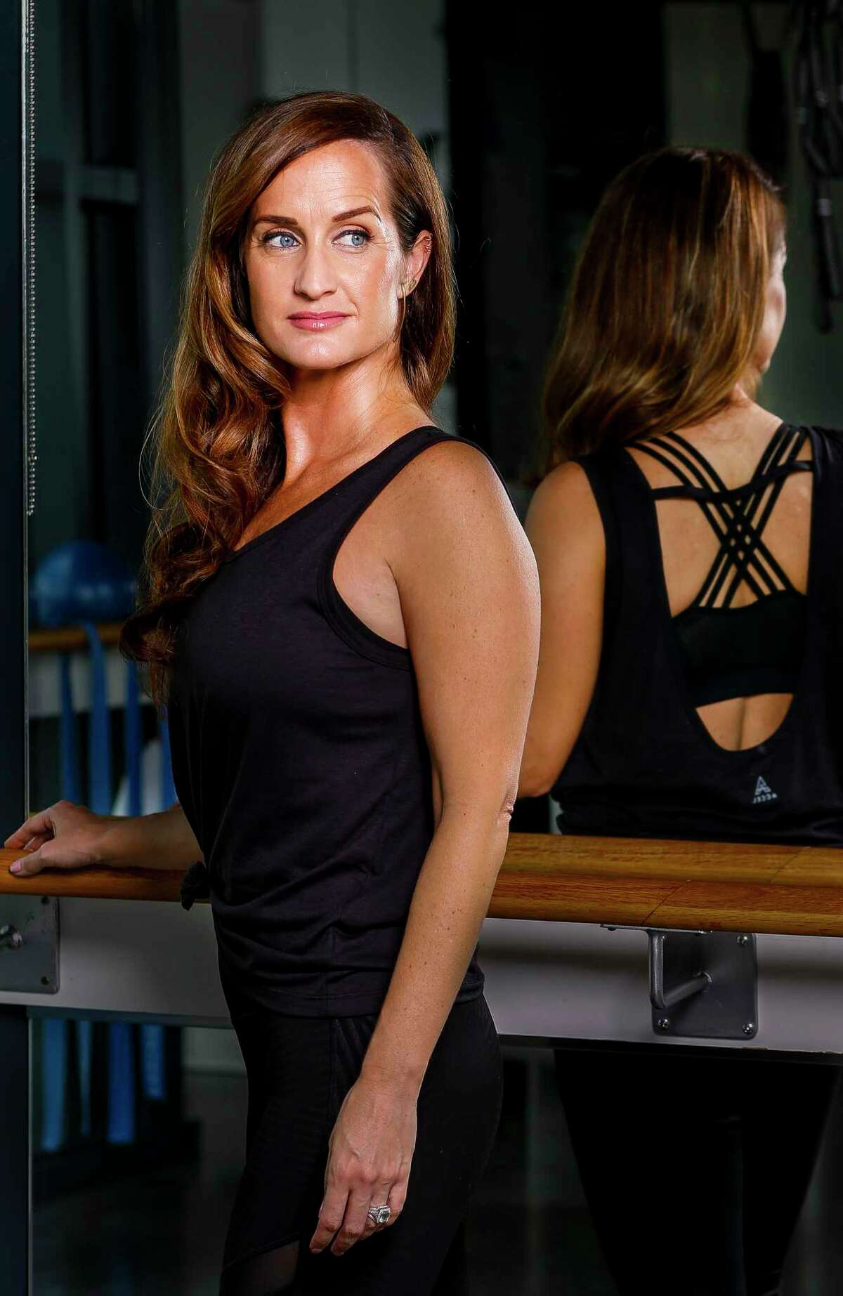 """Megan Eddings, who founded Accel Lifestyle, a clothing company who developed what they call """"anti-stink"""" fabric used in workout clothes, wears one of the company's women's tops at Define studio in the Heights in Houston, Monday, Sept. 30, 2019."""
