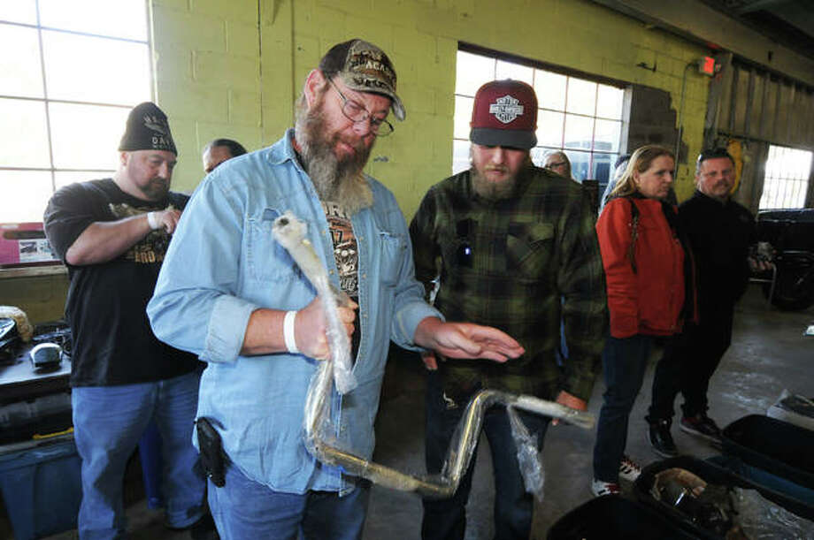 Brian Weyh, of Urbana, and Kyle Larsen, of Collinsville, examine a motorcycle handlebar on Sunday. Photo: David Blanchette|For The Telegraph