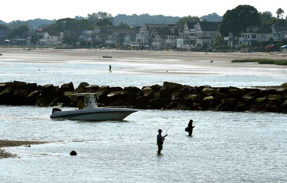 People fish at the mouth of Milford Harbor near Gulf Beach as a boat enters from Long Island Sound on September 11, 2019. Photo: Arnold Gold / Hearst Connecticut Media / New Haven Register