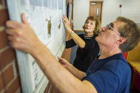 Donna Richards, center, and Robert Lehmann, right, hang a large painting as they work alongside fellow members of the Paint and Palette group to set up their art show Friday, Nov. 1, 2019 on the mezzanine of the Grace A. Dow Memorial Library. The show will run through the month of November, and is dedicated to Dorothy Lynch, a long-time Paint and Palette member who died in February of 2018. (Katy Kildee/kkildee@mdn.net)
