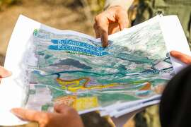 Kellyx Nelson holds a map of the Butano Creek reconnection project in Pescadero, California, on Wednesday, Oct. 16, 2019.