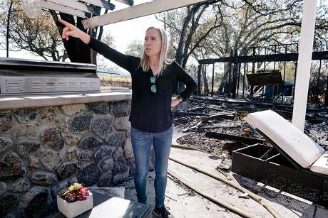 Annie Holden, who's home was spared by the Kincade Fire,  looks round her neighbor's burned property at Chalk's Bend Vineyard in Healdsburg, California, on Monday, November 4th, 2019.