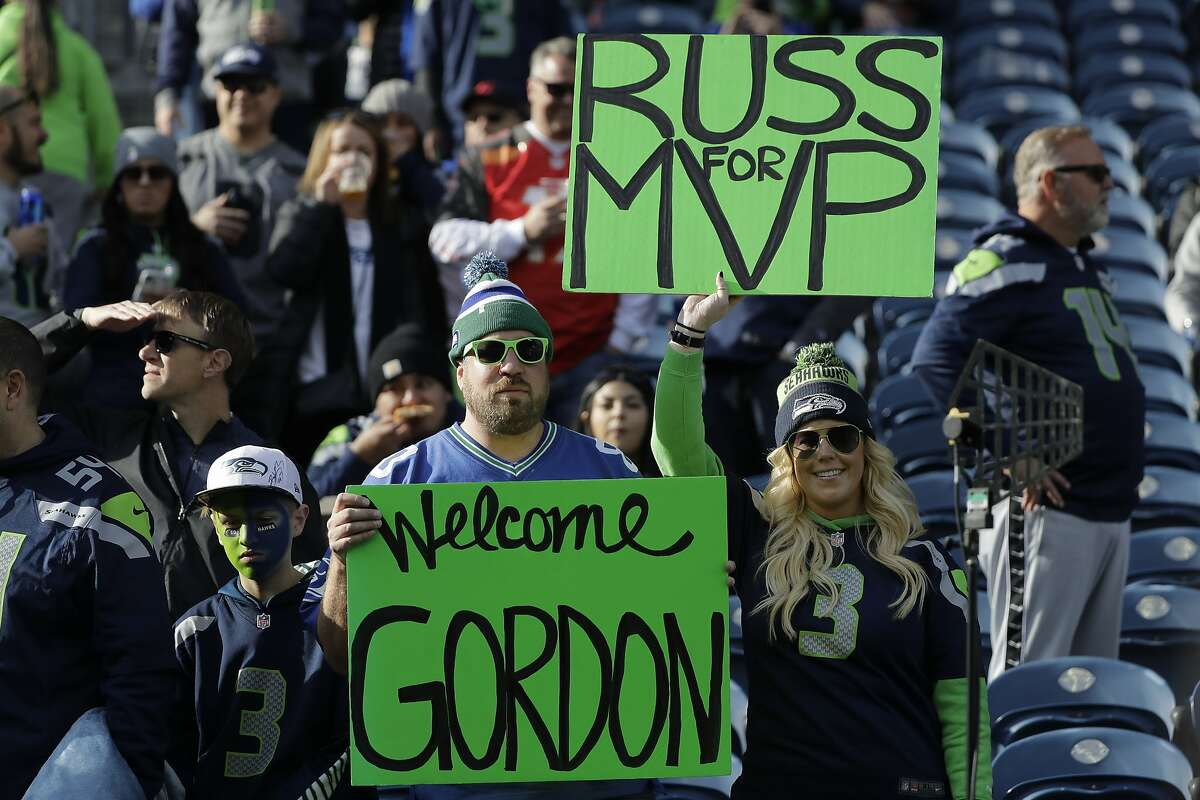 A fan holds a sign welcoming Seattle Seahawks wide receiver Josh Gordon to the team as another fan holds a sign touting quarterback Russell Wilson for the NFL football MVP award before an NFL football game against the Tampa Bay Buccaneers, Sunday, Nov. 3, 2019, in Seattle. (AP Photo/John Froschauer)