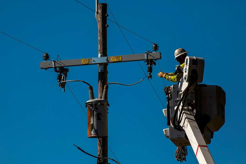 A PG&E contractor works on utility poles along Highway 128 near Geyserville, California on October 31, 2019. (Photo by Philip Pacheco / AFP) (Photo by PHILIP PACHECO/AFP via Getty Images)