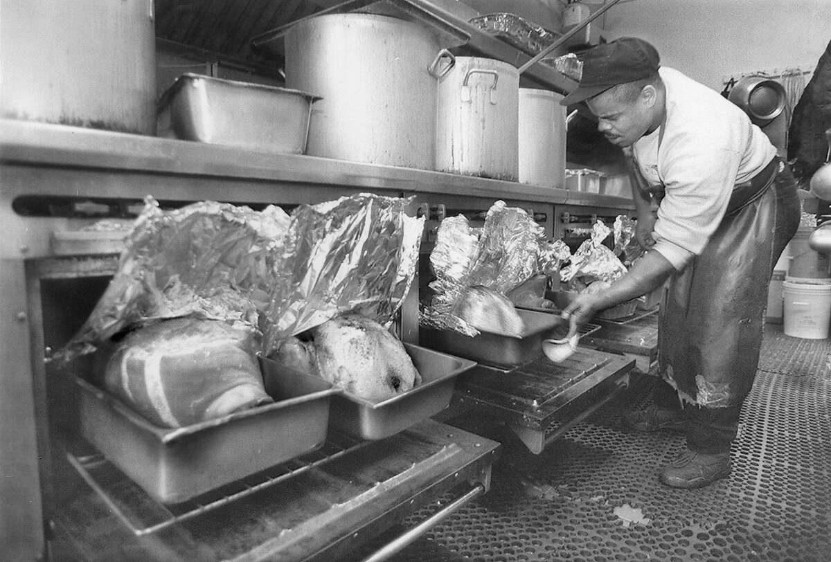 Frank Lipkins, a cook at Glide Memorial checks on the turkeys and hams which will be served for Thanksgiving dinner, November 21, 1994