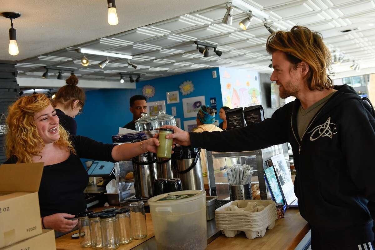 Perch Coffee House barista Laura Nagle serves Brian Stevenson coffee to go in a mason jar on October 30, 2019 in San Francisco, Calif.