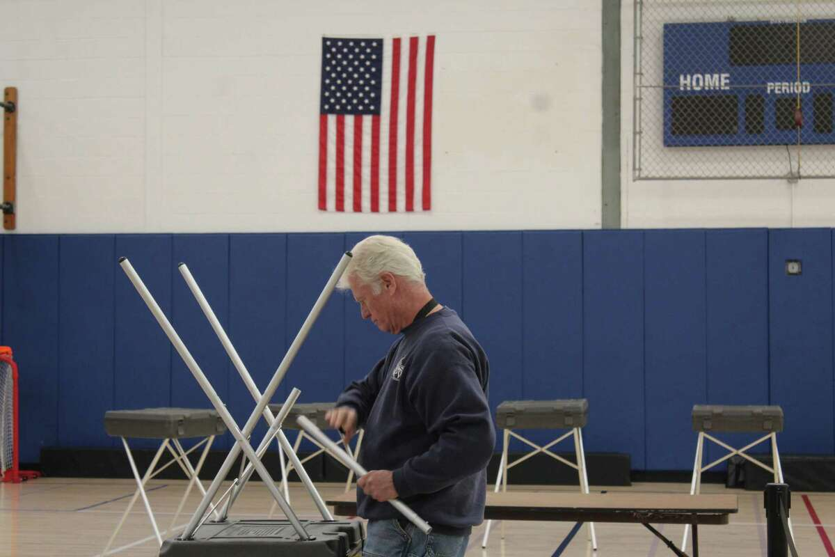 Department of Public Works employee Michael MacDonald sets up a voting booth Monday at Central Middle School, which is the polling place for District 8 in Greenwich.