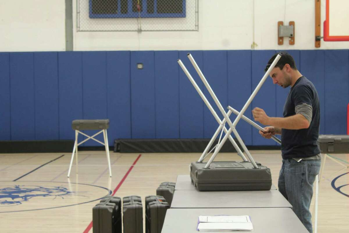 Department of Public Works employee Victor Eimicke sets up a voting booth Monday at Central Middle School, whic is the polling place for District 8 in Greenwich.