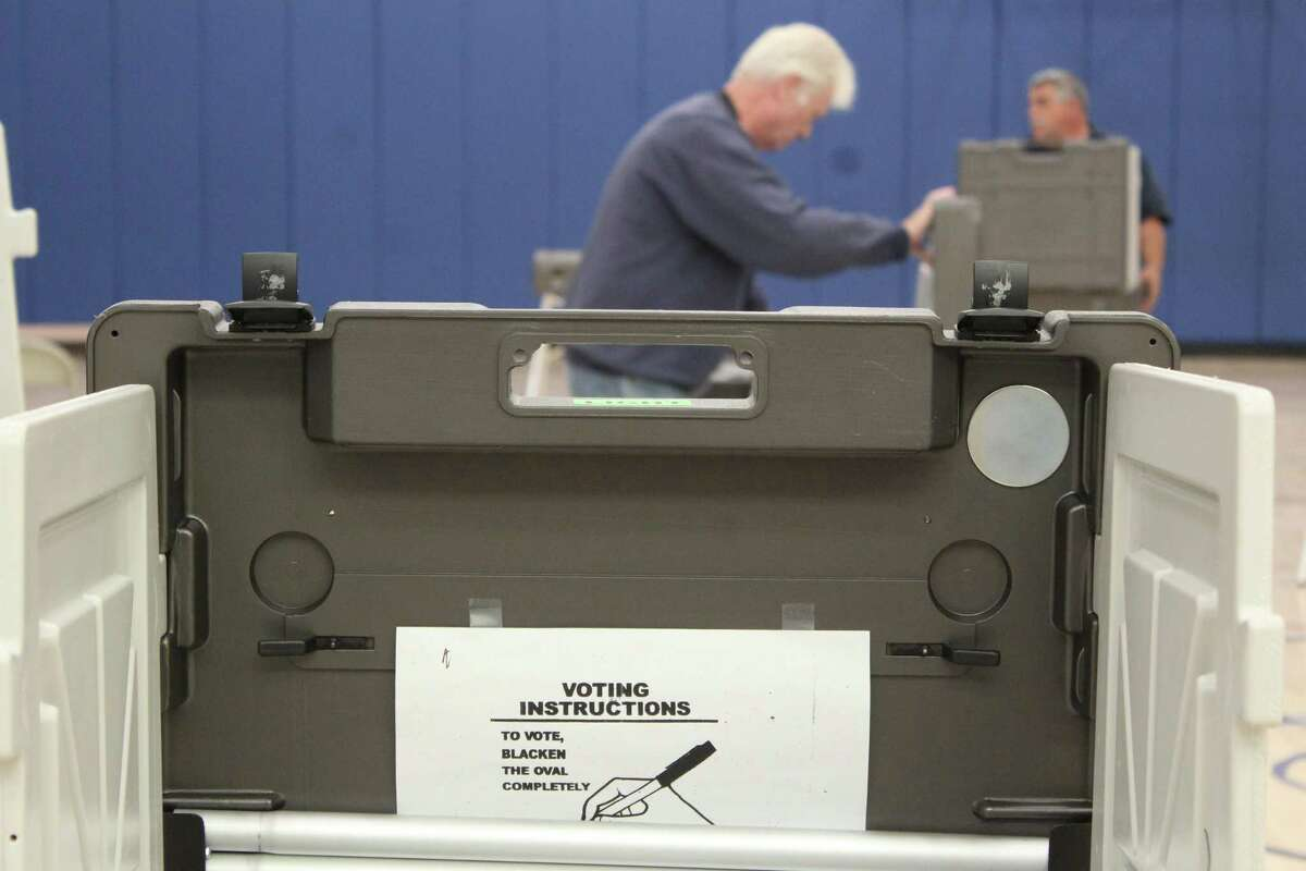 Department of Public Works employee Michael MacDonald sets up a voting booth Monday at Central Middle School, the voting place for District 8 in Greenwich.