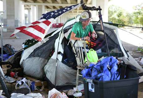 A woman known as Harvest sorts through her possessions to keep before TxDOT workers clear out the homeless camps under Ben White at Westgate in Austin. TxDOT workers followed through with a directive from Gov. Greg Abbott to clean up under highway overpasses in Austin on Monday, Nov. 4, 2019.