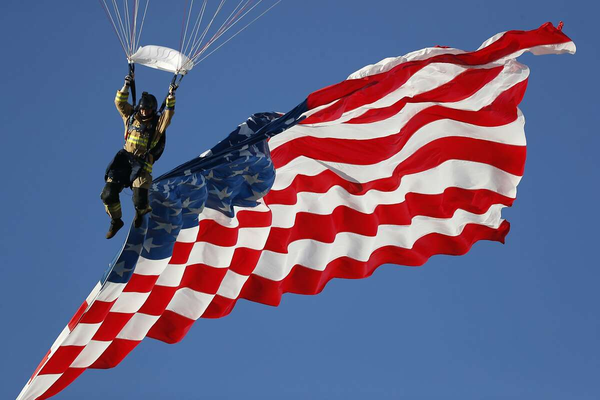 Skydiver guides down the American flag during a jump before the first half of an NCAA college football game between Fresno State Bulldogs and Air Force Falcons Saturday, Oct. 12, 2019, at Air Force Academy, Colo. (AP Photo/David Zalubowski)