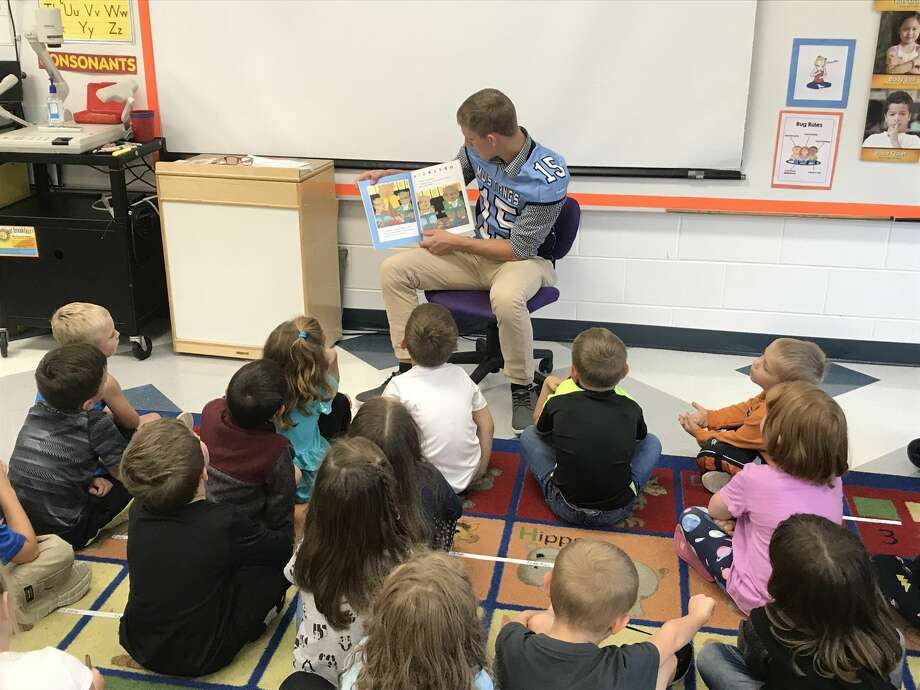 Meridian's Austin North reads aloud to a class of elementary schoolers. Photo: Photo Provided
