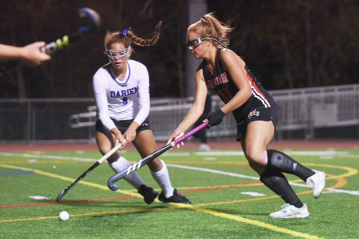 New Canaan's Anna Lindeis (18) and Darien's Raina Johns (9) battle for the ball during their FCIAC field hockey semifinal at Brien McMahon on Monday.