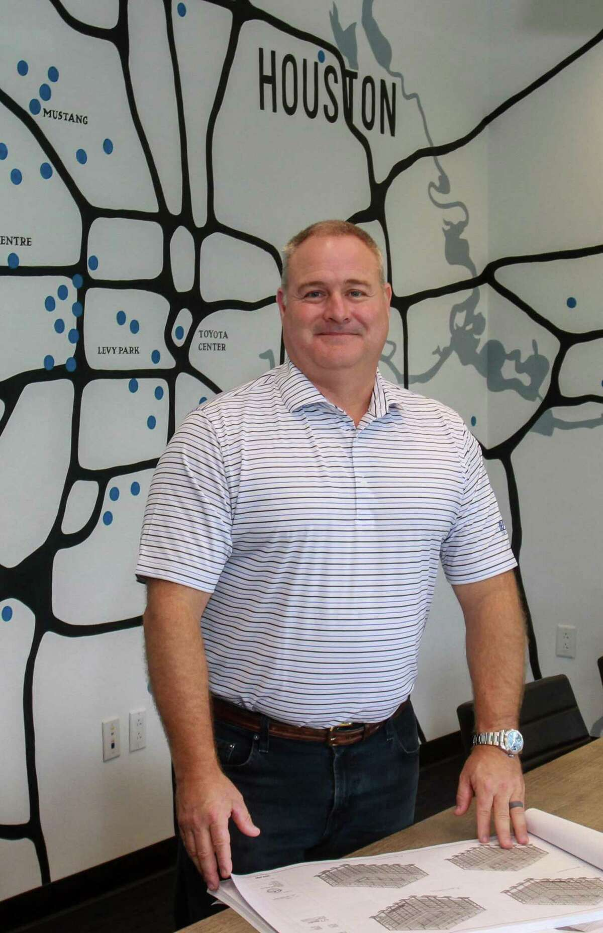 Shawn McAlpin, CEO of Burton Construction in a conference room with a map showing the location of some of their projects in their office in Houston on September 30, 2019.