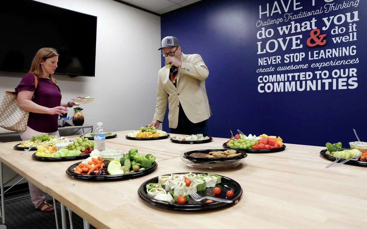 """CB&A realtors Alison McGallion and Quenton Rockwell grab a plate of snacks from a conference room before the start of an """"Open Mic"""" best practices meeting at the office of CB&A Realtors Tuesday, Sept. 17, 2019 in The Woodlands, TX."""