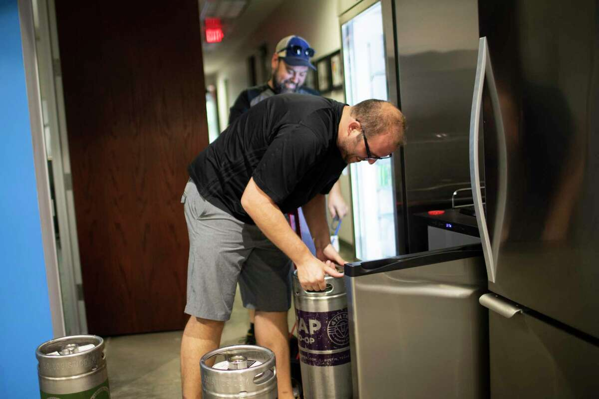 Eric Siebeneich receives a beer delivery from the owner of Jugs Draft, Steve Barron at the Improving - Houston offices on Tuesday, Sept. 10, 2019, in Houston.
