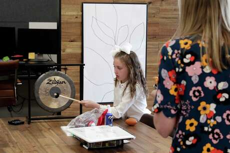 Charlotte Hron (cq), age six, rings a gong normally reserved for celebrating big sales, as her mom Bridget Hron, right, looks on at the monthly team building meeting at ThoughtTrace in their company offices Thursday, Sep. 26, 2019 in Houston, TX.