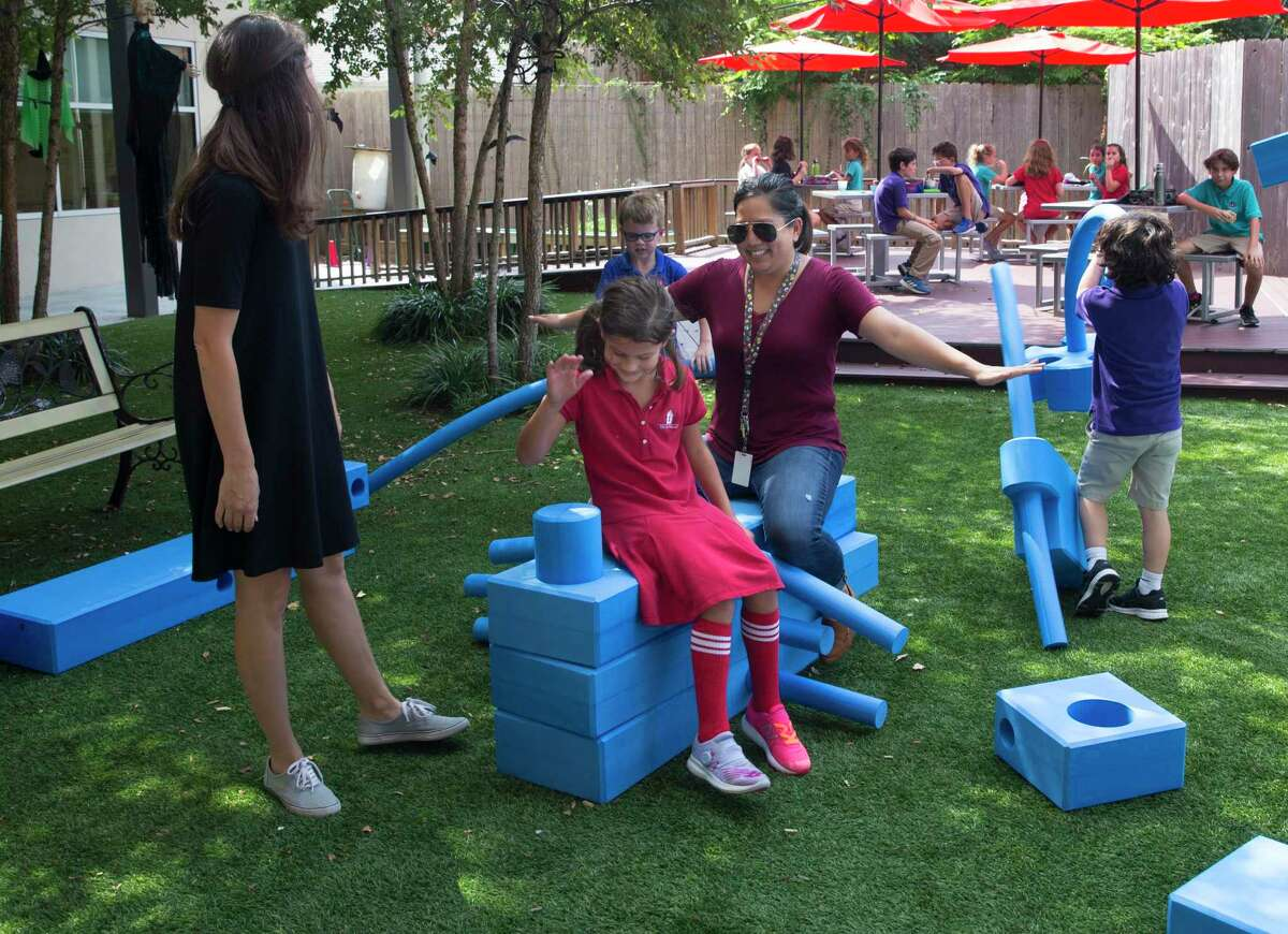 The Joy School Art Teacher Jeannie Do, center, pretends to be flying on an airplane built with blocks with kindergartener Julia Shahda on Thursday, Oct. 3, 2019, in Houston. It is an alternative school for students with learning disabilities and its mission is to get kids to leave and go back to traditional schools.