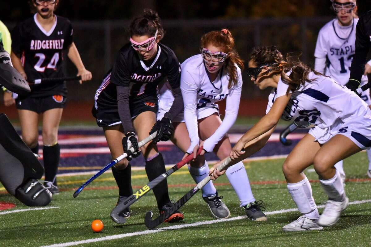 Ridgefield's Olivia DeStefano (11) and Staples' Ella Bloomingdale (9) and Jessica Leon (20) battle for the ball during the FCIAC field hockey semifinals at Brien McMahon on Monday, Nov. 4, 2019.