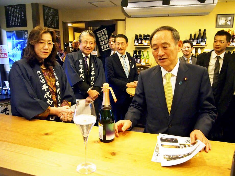Japan's Chief Cabinet Secretary Yoshihide Suga, right, visits a sake brewery in Sakaiminato, Tottori Prefecture, on Monday. Photo: Japan News-Yomiuri / Japan News-Yomiuri