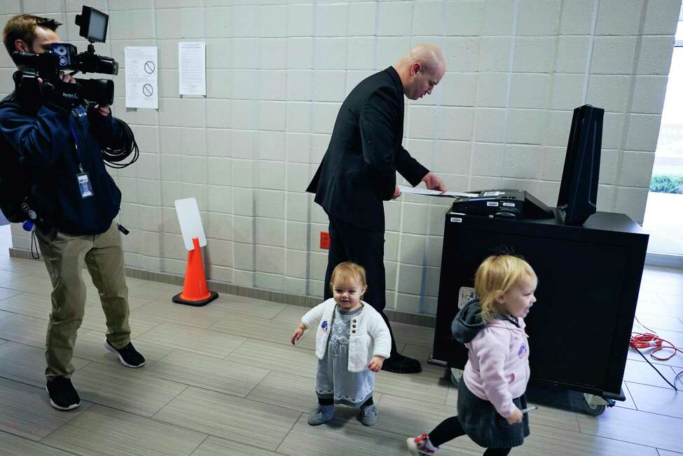 Troy mayoral candidate Tom Reale feeds his ballot into the voting machine as his daughters, Fiammetta, 1, left, and Mackenzie, 3, run around on Tuesday, Nov. 5, 2019, in Troy, N.Y. (Paul Buckowski/Times Union)